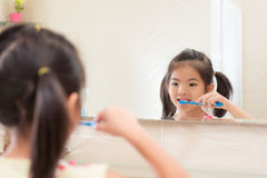 Lovely pretty little kid girl looking at mirror. Reflection image and using toothbrush tool cleaning teeth before go to sleep in bathroom at home Stock Photo