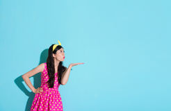 Lovely pretty woman wearing summer dress clothing. Standing on blue background and blowing something to empty area Royalty Free Stock Photo