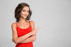 Lovely pretty young woman standing and pointing away in copyspace. Lovely pretty young curly attractive woman in red top standing and pointing away in copyspace stock images