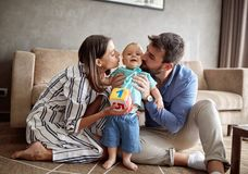 Lovely proud family - mother and father kissing their baby boy. Lovely proud family - mother and father kissing their cute baby boy royalty free stock images