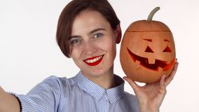 Lovely red lipped woman taking selfies with carved Halloween pumpkin royalty free stock image