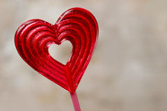 Lovely red lollipop in heart shape. Symbol of sweet love Stock Photos