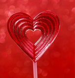 Lovely red lollipop in heart shape. Symbol of sweet love Stock Photography