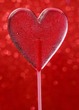 Lovely red lollipop in heart shape. Symbol of sweet love Royalty Free Stock Photo