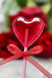 Lovely red lollipop in heart shape. Symbol of sweet love Stock Image