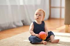 Lovely redhead baby girl with toy ball at home royalty free stock photography