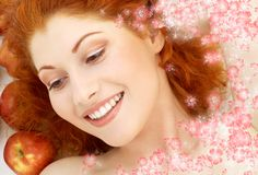 Lovely redhead with red apples and flowers Royalty Free Stock Photo