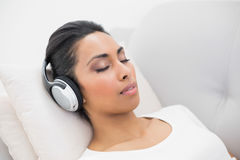 Lovely relaxing woman listening to music while lying on couch Royalty Free Stock Image