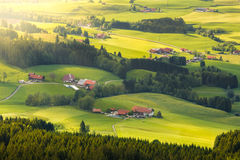 Lovely rural countryside in beautiful sunlight. Pasture landscape with barnyards. Peaceful atmosphere of a typical bavarian cultured landscape Stock Image