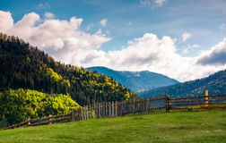 Lovely rural landscape in Carpathians. Wooden fence along the grassy hillside stock photos
