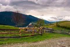 Lovely rural landscape in Carpathians. Wooden fence along the road on a cloudy day in mountains stock photography