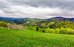 Lovely rural scenery of Carpathians. Beautiful landscape with grassy rural fields on hills in springtime. overcast sky over the mountains stock images