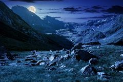 Lovely scenery of Transfagarasan valley at night. Lovely scenery of Transfagarasan road in valley at night in full moon light. rocks on grassy meadow and slopes stock image