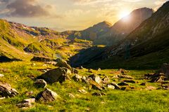 Lovely scenery of Transfagarasan valley at sunset. Lovely scenery of Transfagarasan road in valley at sunset. rocks on grassy meadow and slopes. half of the Stock Photography
