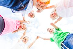 Lovely schoolchildren standing in a circle holding hands up stock photography