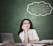 Lovely schoolgirl daydreaming about future jobs Royalty Free Stock Photo