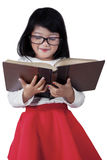 Lovely schoolgirl reading a book in studio Royalty Free Stock Photos