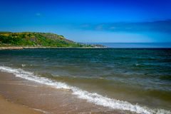 Lovely Scottish beach with bright blue sky and bright green hills in background with water splashing in foreground. Lovely scottish beach bright blue sky green royalty free stock photos