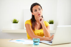 Lovely secretary wondering while sitting in office Royalty Free Stock Photos