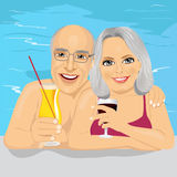 Lovely senior couple drinking red wine and cocktail in pool Stock Image