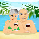 Lovely senior couple drinking red wine lying on the beach Stock Photography