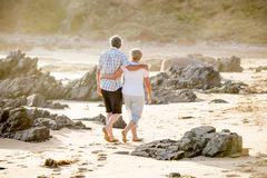 Lovely senior mature couple on their 60s or 70s retired walking happy and relaxed on beach sea shore in romantic aging together an Royalty Free Stock Photos