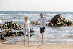 Lovely senior mature couple on their 60s or 70s retired walking happy and relaxed on beach sea shore in romantic aging together Stock Photo