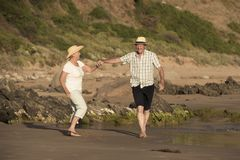 Lovely senior mature couple on their 60s or 70s retired walking happy and relaxed on beach sea shore in romantic aging together Stock Images