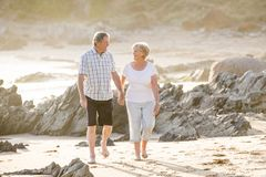 Lovely senior mature couple on their 60s or 70s retired walking happy and relaxed on beach sea shore in romantic aging together Stock Photography