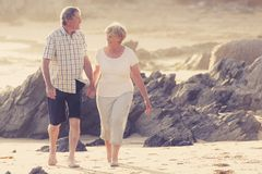 Lovely senior mature couple on their 60s or 70s retired walking happy and relaxed on beach sea shore in romantic aging together Royalty Free Stock Photos