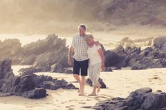 Lovely senior mature couple on their 60s or 70s retired walking happy and relaxed on beach sea shore in romantic aging together. And retirement husband and wife Stock Photography