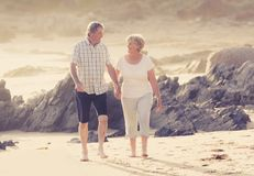 Lovely senior mature couple on their 60s or 70s retired walking happy and relaxed on beach sea shore in romantic aging together. And retirement husband and wife Royalty Free Stock Images