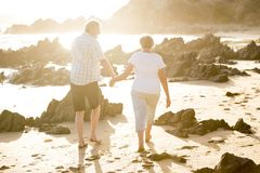 Lovely senior mature couple on their 60s or 70s retired walking happy and relaxed on beach sea shore in romantic aging together. And retirement husband and wife Stock Photo