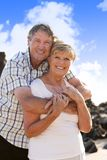 Lovely senior mature couple on their 60s or 70s retired walking happy and relaxed outdoors under a blue sky in love romantic aging. Together and retirement Royalty Free Stock Photography