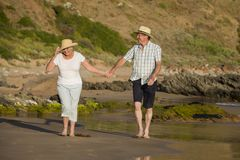 Lovely senior mature couple on their 60s or 70s retired walking happy and relaxed on beach sea shore in romantic aging together Stock Photos