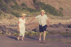 Lovely senior mature couple on their 60s or 70s retired walking happy and relaxed on beach sea shore in romantic aging together Royalty Free Stock Photography