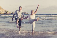 Lovely senior mature couple on their 60s or 70s retired walking happy and relaxed on beach sea shore in romantic aging together Stock Image