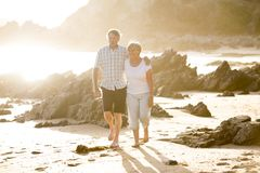 Lovely senior mature couple on their 60s or 70s retired walking happy and relaxed on beach sea shore in romantic aging together. And retirement husband and wife Stock Image