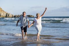 Lovely senior mature couple on their 60s or 70s retired walking happy and relaxed on beach sea shore in romantic aging together. And retirement husband and wife Royalty Free Stock Image