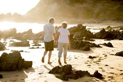 Lovely senior mature couple on their 60s or 70s retired walking happy and relaxed on beach sea shore in romantic aging together. And retirement husband and wife Royalty Free Stock Photos