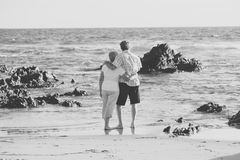 Lovely senior mature couple on their 60s or 70s retired walking happy and relaxed on beach sea shore in romantic aging together Royalty Free Stock Image
