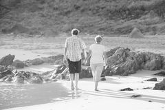 Lovely senior mature couple on their 60s or 70s retired walking happy and relaxed on beach sea shore in romantic aging together Royalty Free Stock Images
