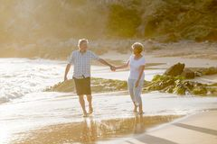 Lovely senior mature couple on their 60s or 70s retired walking Stock Photos