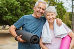 Happy senior couple with yoga mat royalty free stock photography