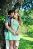 Lovely sensual couple in love enjoying kiss outdoors. In warm summer day in the city park Royalty Free Stock Images