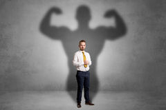 Businessman with muscular shade behind his back Stock Photo