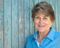 Lovely Seventy Year Old Woman Smiling in Blue Shir. Headshot of a senior woman with blue eyes in a blue shirt against a rustic blue wall with room for text Royalty Free Stock Photos