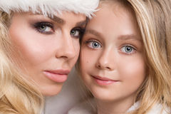 Lovely sexy blond mother with a baby girl daughter dressed as Santa Claus Stock Photo