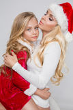 Lovely sexy blond mother with a baby girl daughter dressed as Santa Claus Royalty Free Stock Photos