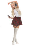 Lovely sexy blonde girl in checkered short skirt with headphones Royalty Free Stock Image